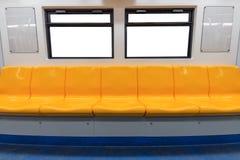 Gele stoel en vensters in elektrische trein stock afbeelding
