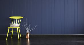 Gele stoel met boeken op lege donkere houten muurachtergrond Royalty-vrije Stock Foto's