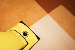 Gele stofzuiger op een tapijt Stock Afbeelding