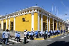Gele straathoek en studenten in eenvormig, Arequipa, Peru