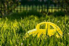 Gele stuk speelgoed auto en groen gazon stock fotografie
