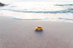Gele stuk speelgoed auto op het strand in het zonlicht in de zomer Vakantie en reisconcept royalty-vrije stock afbeelding
