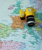 Gele stuk speelgoed camera op de kaart van Europa en Italië Stock Foto's