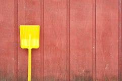 Gele stuk speelgoed schop tegen rode schuurmuur Royalty-vrije Stock Foto's