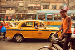 Gele taxiauto, bussen en fietsers die op de bezige straat van Indische stad drijven royalty-vrije stock foto