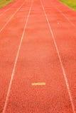 Gele tekens Witte lijnen en textuur van het runnen van renbaan, rode renbaan, in openluchtstadion Stock Foto's