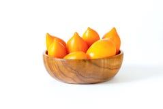 Gele tomaten in een houten kom royalty-vrije stock afbeeldingen