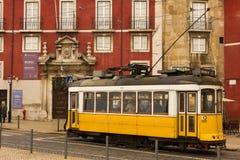Gele tram die door het Azurara-Paleis overgaan. Lissabon. Portugal Stock Afbeeldingen