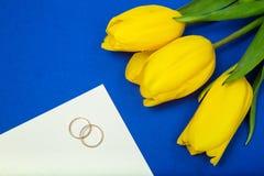 Gele tulpen en trouwringen Stock Foto