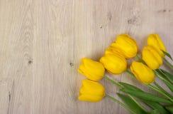 Gele tulpen op een houten lijst, Pasen-achtergrond Stock Afbeeldingen