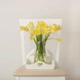 Gele tulpen in vaas op wit dienblad op de stoel royalty-vrije stock afbeelding