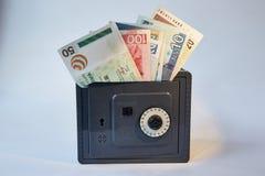 Gele van metaaldollars en rekeningen verschillende geïsoleerde munten in grijze brandkast, stock foto