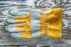 Gele veiligheidshandschoenen op houten raad Stock Afbeelding