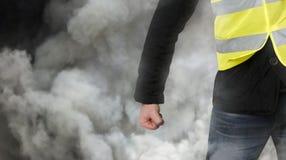Gele vestenprotesten De onherkenbare mens klemde zijn vuist in protest in traangas dicht Het concept revolutie en protest, de str stock afbeelding