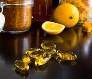 Gele vitaminecapsules, op achtergrondcitroen Stock Foto