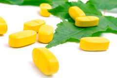 Gele vitaminepillen over groen verlof Royalty-vrije Stock Fotografie