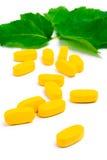 Gele vitaminepillen over groene bladeren Royalty-vrije Stock Afbeeldingen