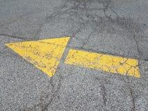 Gele wijzerpijl op zwart asfalt met barsten royalty-vrije stock afbeeldingen