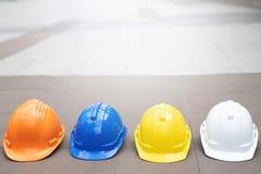 Gele, witte, blauwe harde de helmhoed van de veiligheidsslijtage in het project bij bouwwerf royalty-vrije stock afbeeldingen