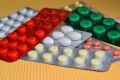 Gele, witte, rode, groene ronde en ovale medische die tabletten in pak, tabletten in blaren worden ingepakt stock fotografie