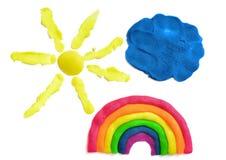 Gele zon, blauwe die wolk en regenboog van plasticine wordt gemaakt, op de witte achtergrond wordt geïsoleerd Stock Foto's