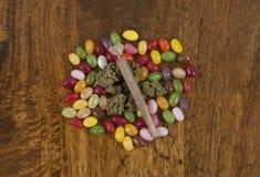 Geleebonbone und Hanf Sativa, vorbereitet für munchies beim Rauchen des Unkrautgelenkes stockfotografie