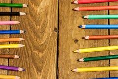 gelegentliche bunte Bleistifte auf altem Holztisch Lizenzfreie Stockfotografie
