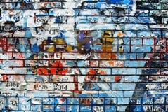 Gelegentliche Hintergrundcollagen-Papierbeschaffenheit auf Backsteinmauer Lizenzfreie Stockfotos