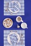 Gelegte Tabelle - Gabel und Löffel legten auf blauen Stoff und weiße Platte Stockfoto