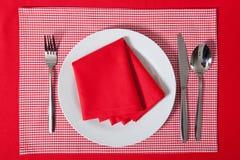Gelegte Tabelle - Gabel und Löffel legten auf roten Stoff und weiße Platte Stockfoto