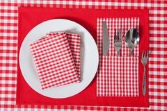 Gelegte Tabelle - Gabel und Löffel legten auf roten Stoff und weiße Platte Lizenzfreies Stockfoto