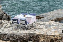 Gelegte Tabelle und Stühle an einem Restaurant durch das Meer Lizenzfreie Stockbilder