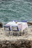 Gelegte Tabelle und Stühle an einem Restaurant durch das Meer Lizenzfreies Stockbild