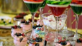 A geleia e o souffle coloridos da sobremesa do fruto no projeto comemorativo de vidro do alimento do jantar deslizam o movimento vídeos de arquivo