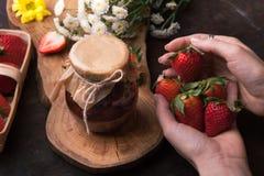 Geleiaardbei op de houten achtergrond met bloemen Vrouwelijke handen die het houden van een aardbei houden Stock Afbeelding