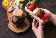 Geleiaardbei op de houten achtergrond met bloemen Vrouwelijke handen die mand met aardbeien houden Stock Foto