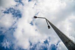 Geleide straatlantaarn op concrete pylon, blauwe hemel met witte wolken op de achtergrond stock fotografie