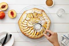 Geleidelijke receptengalette of pastei met nectarines De vrouwelijke handen bestrooien een pastei van gepoederde suiker Royalty-vrije Stock Fotografie