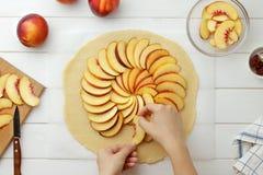Geleidelijke receptengalette of pastei met nectarines De vrouwelijke handen maken plakken van nectarine op het deeg op Stock Afbeelding