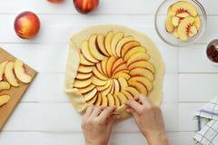 Geleidelijke receptengalette of pastei met nectarines Vrouwelijke handen die deeg` s randen verpakken rond het vullen Royalty-vrije Stock Afbeeldingen