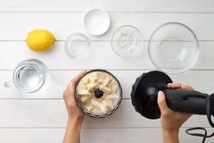 Geleidelijke receptengalette of pastei met nectarines Vrouwelijke handen die een deeg met mixer kneden Stock Afbeelding