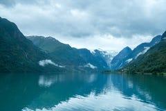 Geleira de Briksdal atrás do lago da montanha com reflexão em Briksdalbreen, Noruega foto de stock