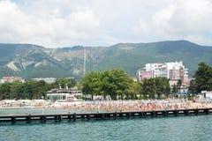 Gelendzhik,俄罗斯人在与山的海滩放松在背景中 免版税库存照片