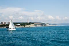 Gelendzhik,俄罗斯有一个风帆的一条小船在背景厚实的海角的海 库存照片