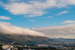 Gelendzhik mountains panorama with low lying clouds before wind and city buildings. Copy space stock image