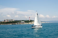 Gelendzhik, Russia a boat with a sail on the sea in the background thick Cape Stock Photo