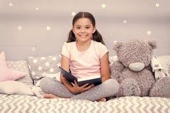 Gelesene M?rchen vorher schlafen gehen M?dchenkind sitzen Bett mit Teddyb?r gelesenem Buch Kind bereiten vor sich schlafen zu geh stockfotos