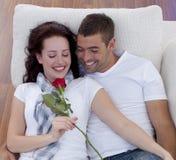 Geliebte auf Sofa mit einer Rose stockfotografie
