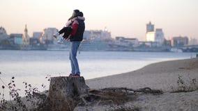 geliebte Der Junge zieht das Mädchen in seinen Armen auf Eine Paarstellung auf einem Stumpf vor dem hintergrund des Flusses 4K la stock video footage