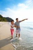 Geliebte, die entlang den Strand gehen Lizenzfreies Stockfoto
